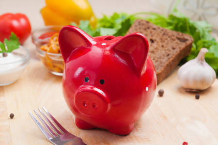 Tisch mit rotem Sparschwein und Gemüse im Hintergrund
