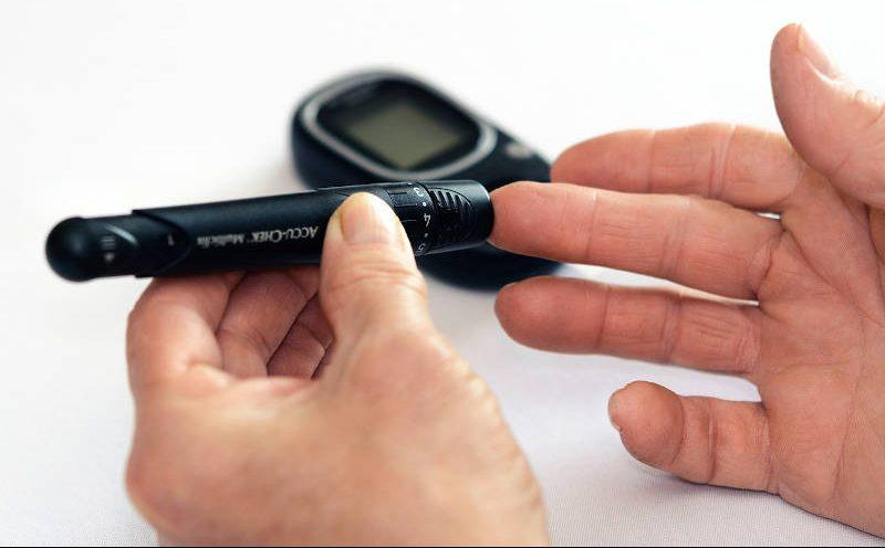 Mann misst mit Messgerät seinen Blutzucker