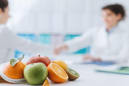 Beratungsgespräch einer Ernährungsberaterin mit Obst im Vordergrund