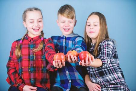Drei lächelnde Kinder mit jeweils einem Apfel in der Hand