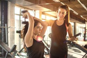Fitnesstrainerin trainiert Kundin an Übungsgerät