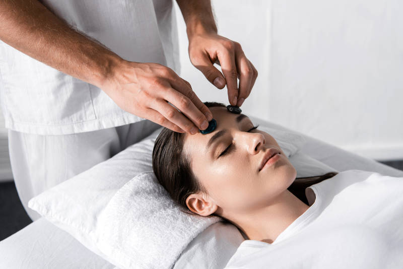 Heilpraktiker behandelt Patient mit Steinen