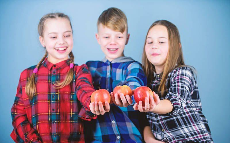 Drei Kinder mit jeweils einem Apfel in der Hand