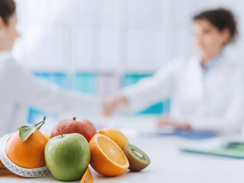 Ernährungsberater betreut Kunde mit frischem Obst