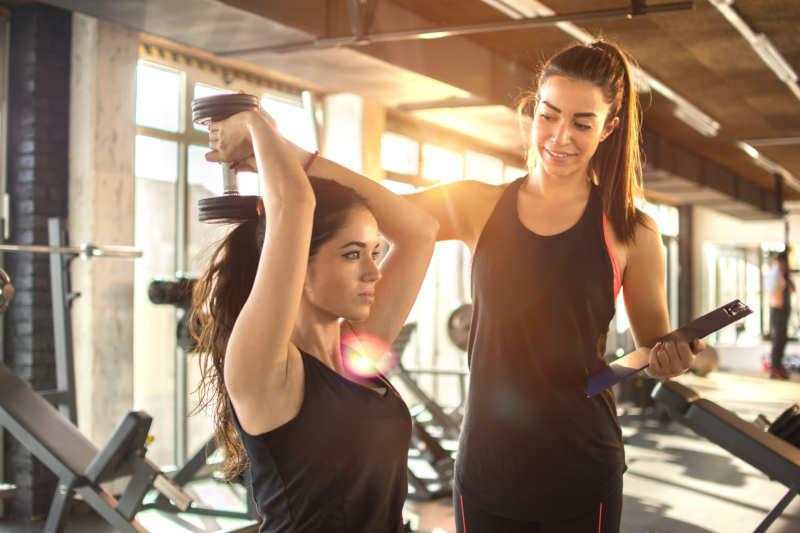 Fitnesstrainerin trainiert Frau an Übungsgerät