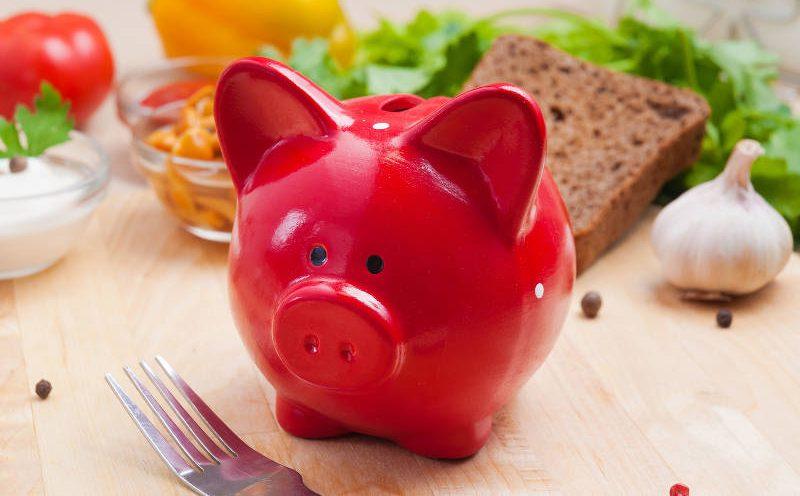Rotes Sparschwein mit gesunden Lebensmitteln im Hintergrund